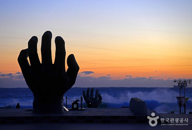 韓國跨年 後的曙光中的手剪影