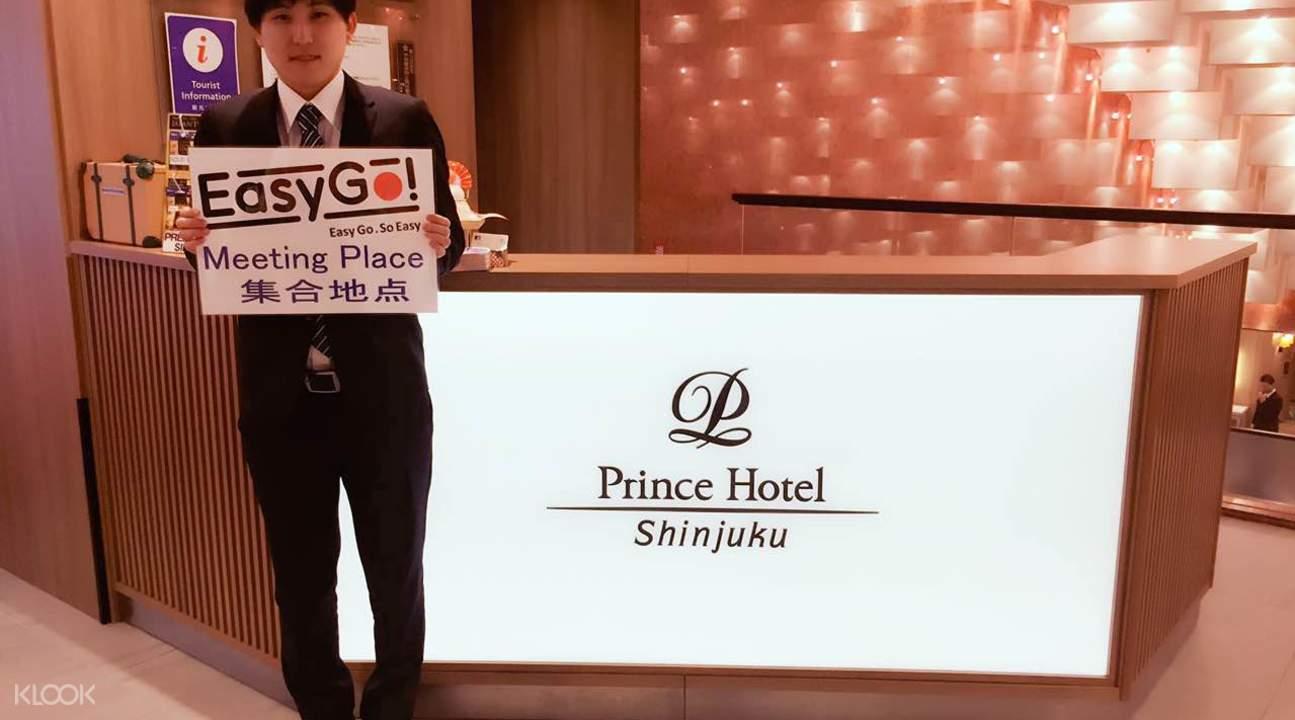 集合地點位於新宿王子飯店,服務人員拿著指示牌。
