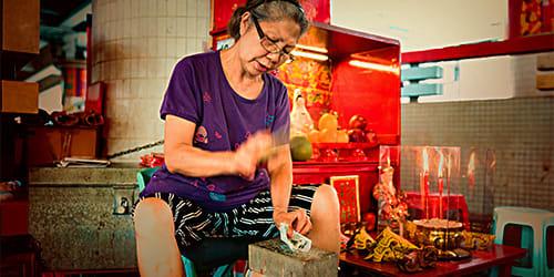 神婆正在用拖鞋進行打小人儀式。﹝圖片取自香港旅遊發展局官網﹞