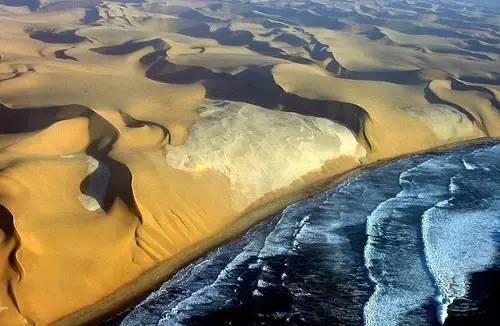 從 空 中 俯 瞰 , 骷 髏 海 岸 是 一 大 片 摺 痕 斑 駁 的 金 色 沙 丘 。