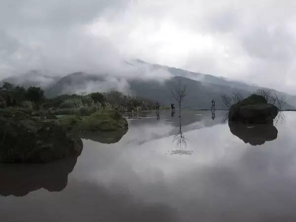 如 一 片 明 鏡 , 照 映 著 山 巒 與 雲 霧