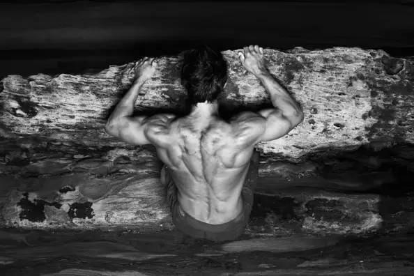 大 秀 肌 肉 的 攀 岩 者 。