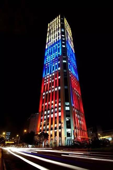 大 樓 外 牆 上 閃 耀 著 哥 倫 比 亞 國 旗 顏 色 的 燈 光 。