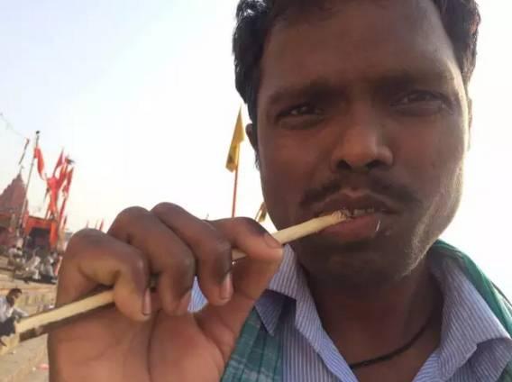 在 恒 河 邊 拿 樹 枝 刷 牙 的 印 度 大 哥。