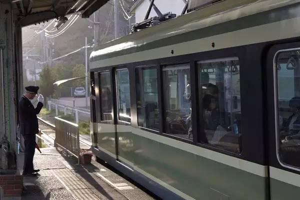 △ 晨 光 中 列 車 緩 緩 離 站 , 車 站 和 列 車 上 的 工 作 人 員 互 相 行 禮 。