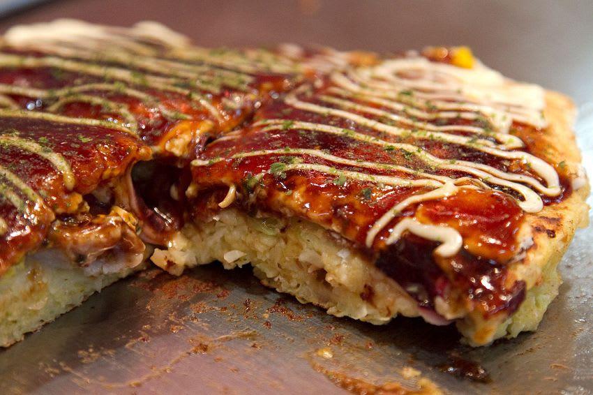剛 說 完 明 石 燒 , 第 四 名 就 是 大 家 耳 熟 能 詳 的 大 阪 燒 , 將 所 有 食 材 放 在 一 起 煎 成 餅 , 淋 上 可 口 醬 汁 , 旅 客 們 還 可 以 自 己 體 驗 煎 盤 的 樂 趣 。( 圖 / Booking.com 提 供 )