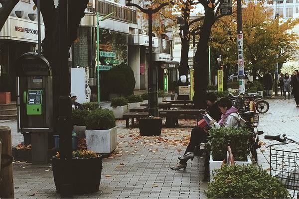 坐 在 路 邊 看 書 的 路 人 。