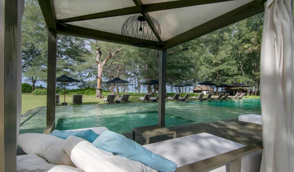 giường nghỉ dưỡng bên hồ bơi của  SALA Phuket Resort & SPA