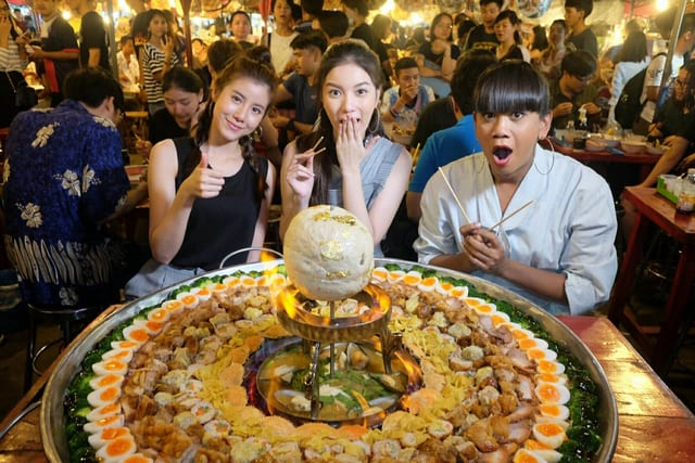 People with giant thai noodle dish