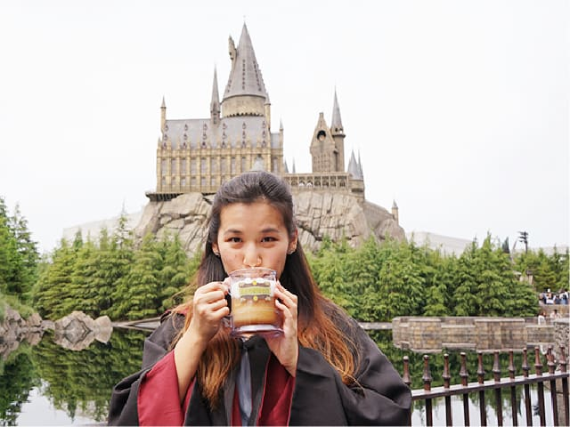 Drinking Butterbeer in front of the Hogwarts castle