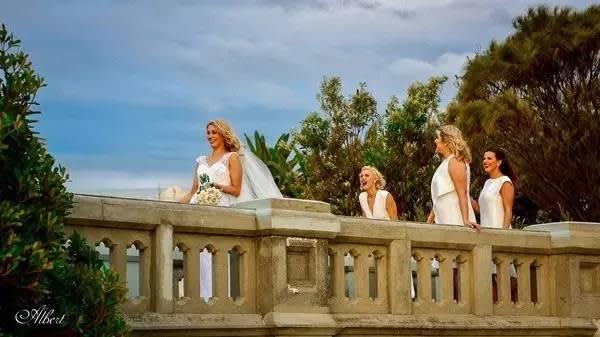有 披 著 白 紗 的 美 麗 新 娘 和 伴 娘 團 , 在 夕 陽 下 開 心 的 笑 著 。