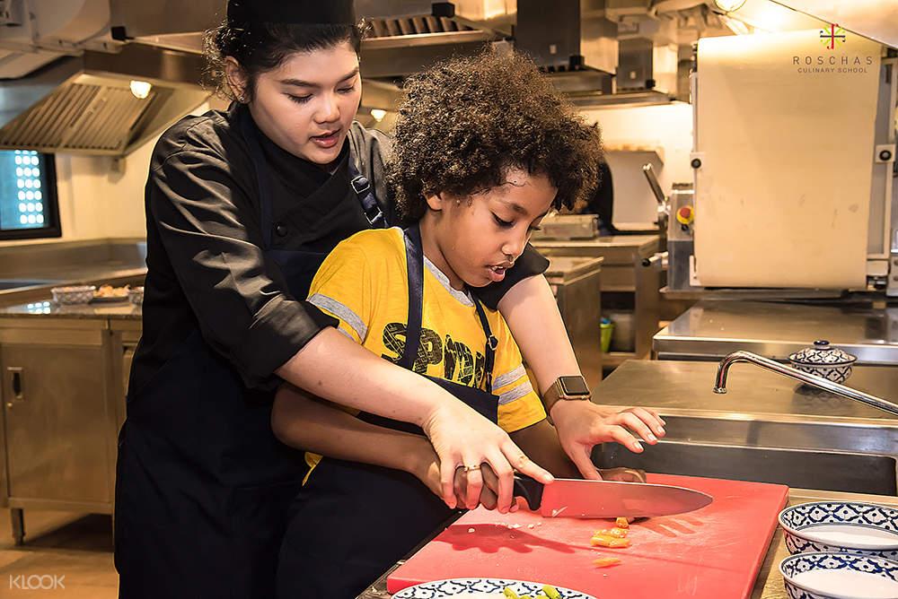 chef mengajari anak-anak mengunakan pusau