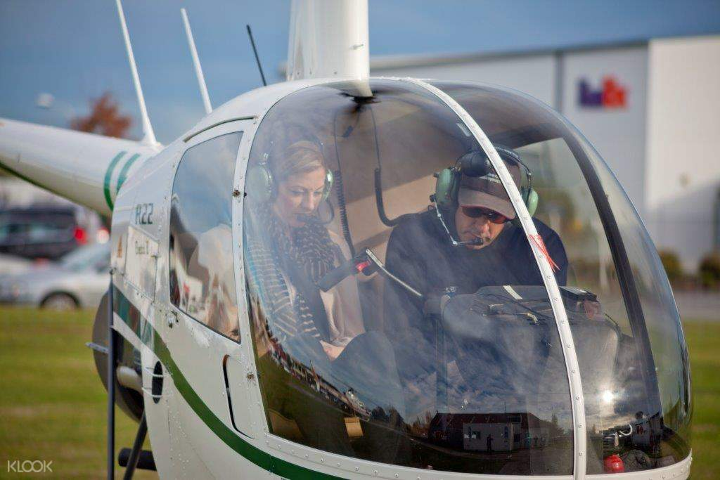 woman and guide inside a helicopter