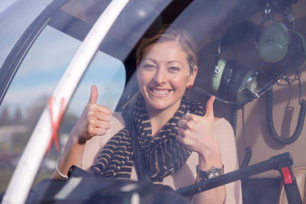 a woman with 2 thumbs up inside a helicopter