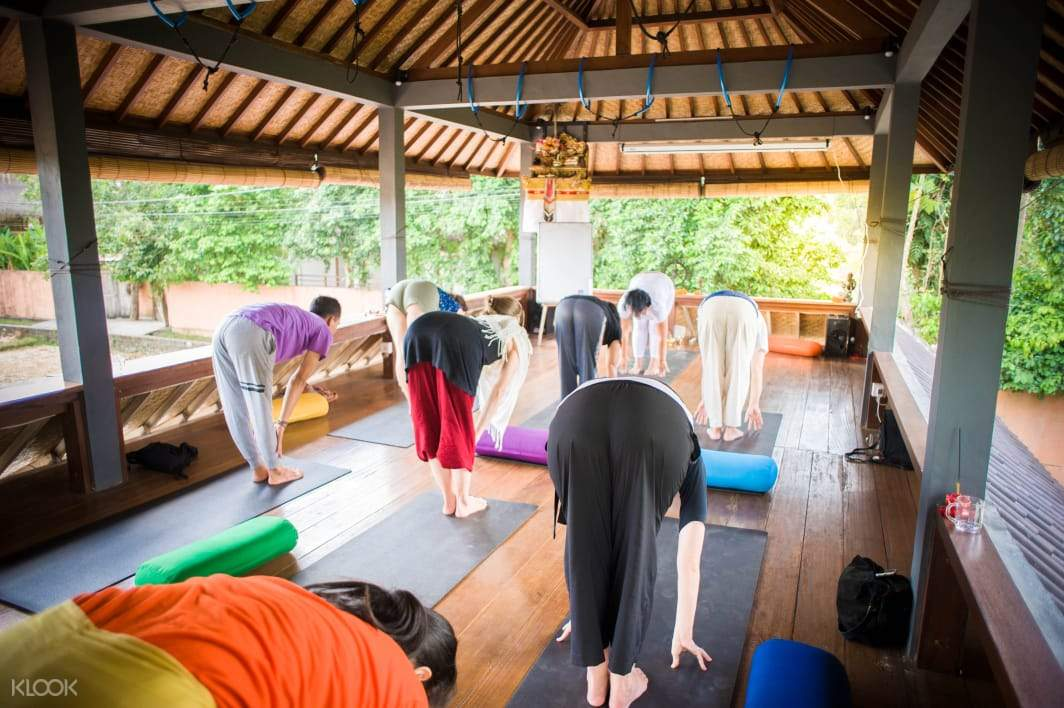 yoga students and instructor leg stretching