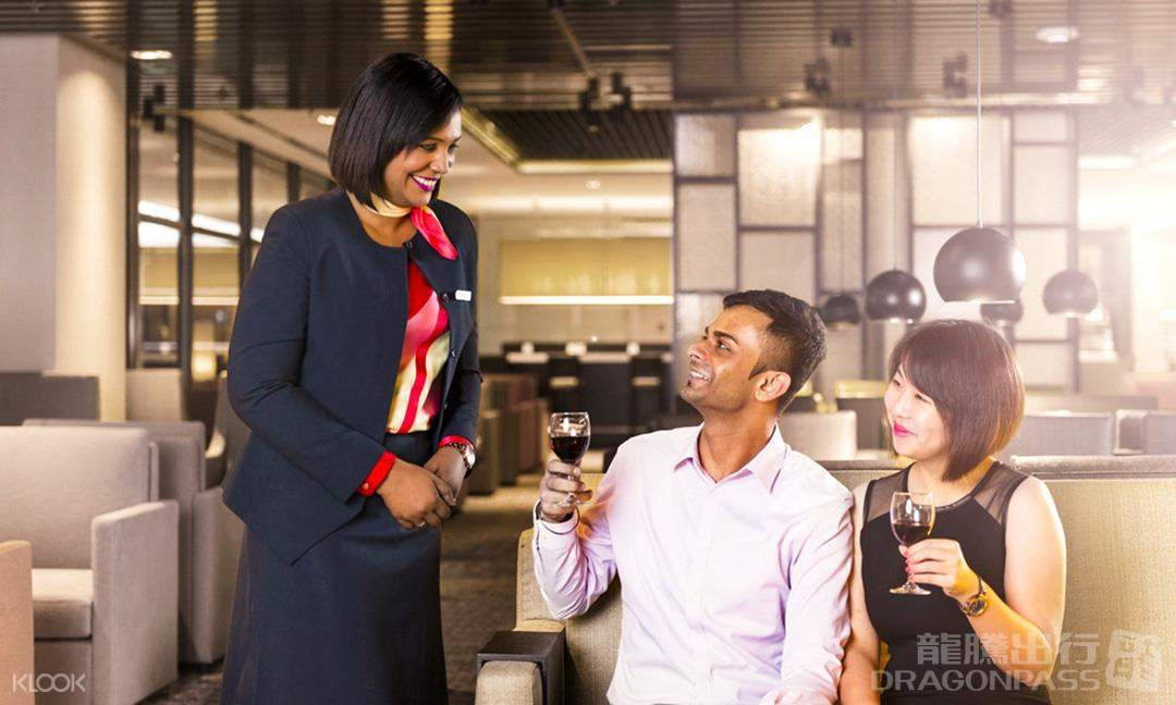 female staff with customers drinking wine at singapore changi airport lounge