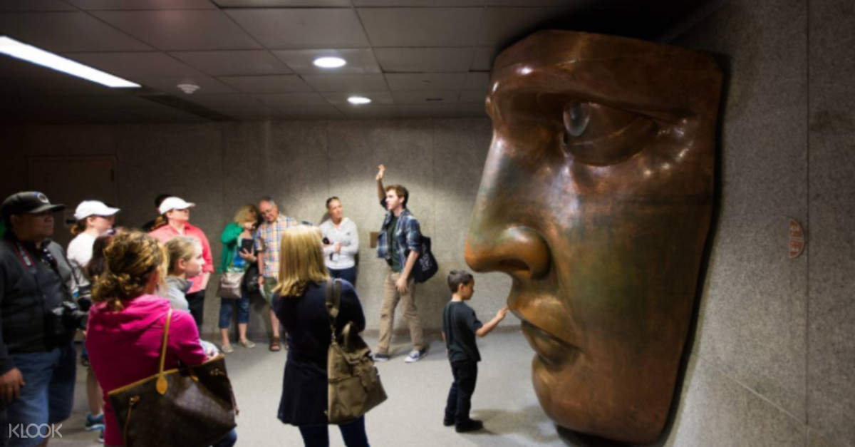 crowd of people looking at aface sculpture inside the museum