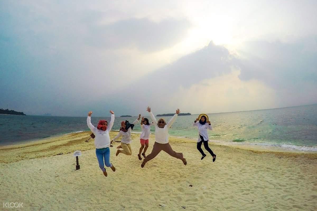 tourists jumping on beach
