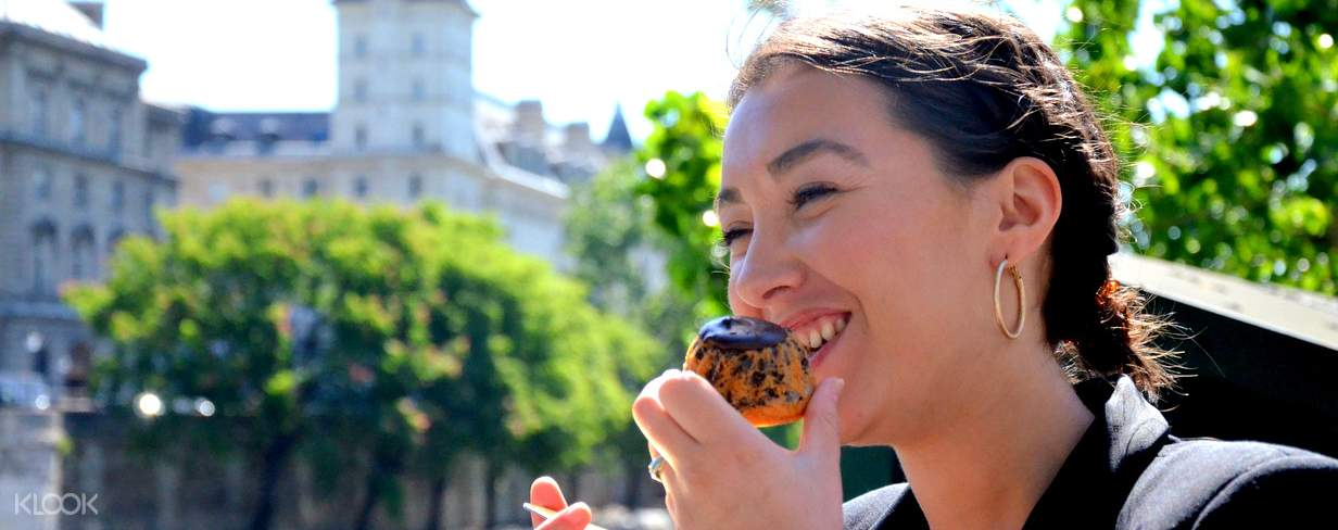 woman eating a bread in paris