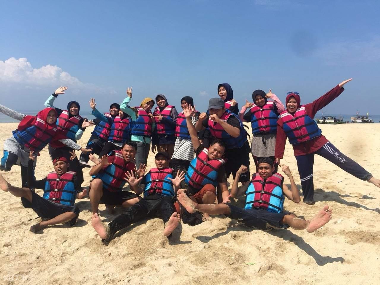 rombongan wisatawan berpose di pantai