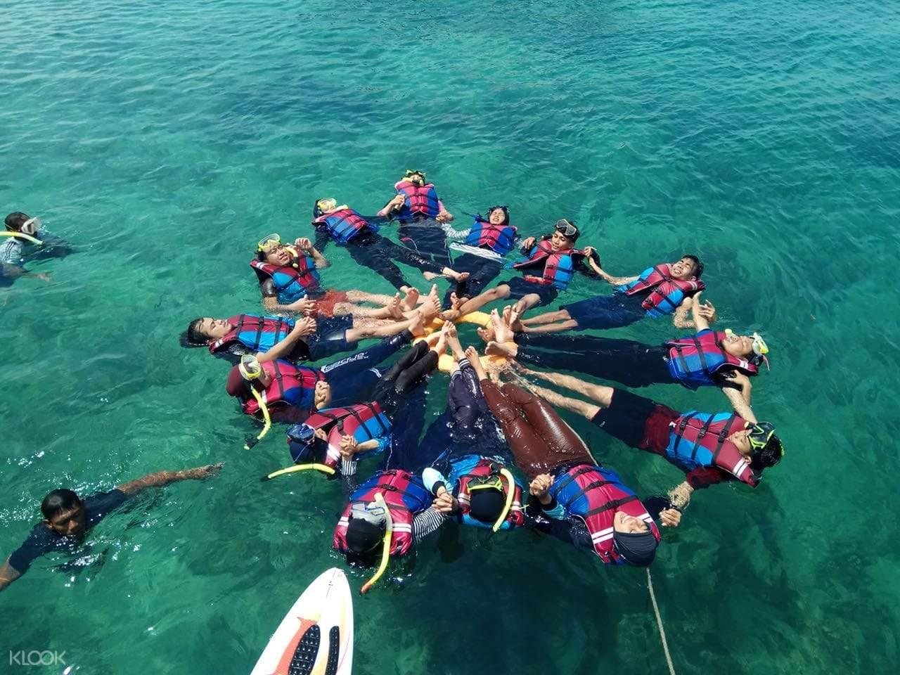 wisatawan mengapung di atas air dalam bentuk lingkaran