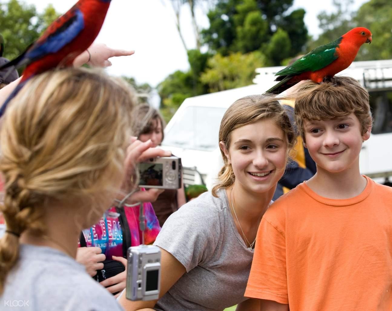 a girl and a boy posing with a bird on the boy's head