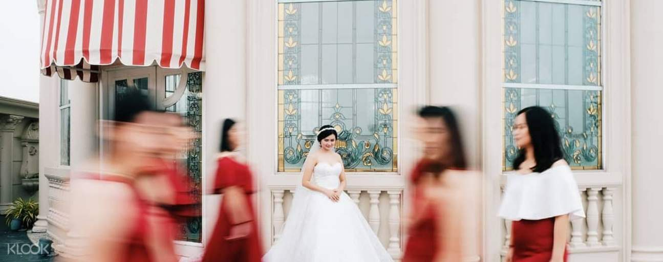 Woman in bridal dress in front of store