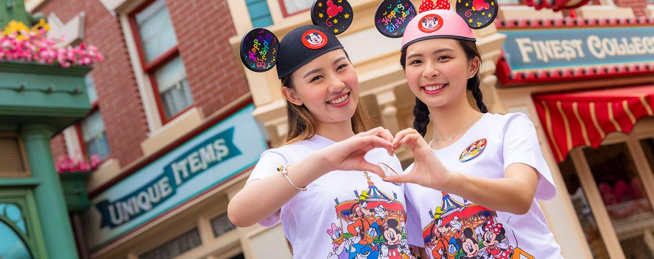 two women in Disney merchandise shirts and hats