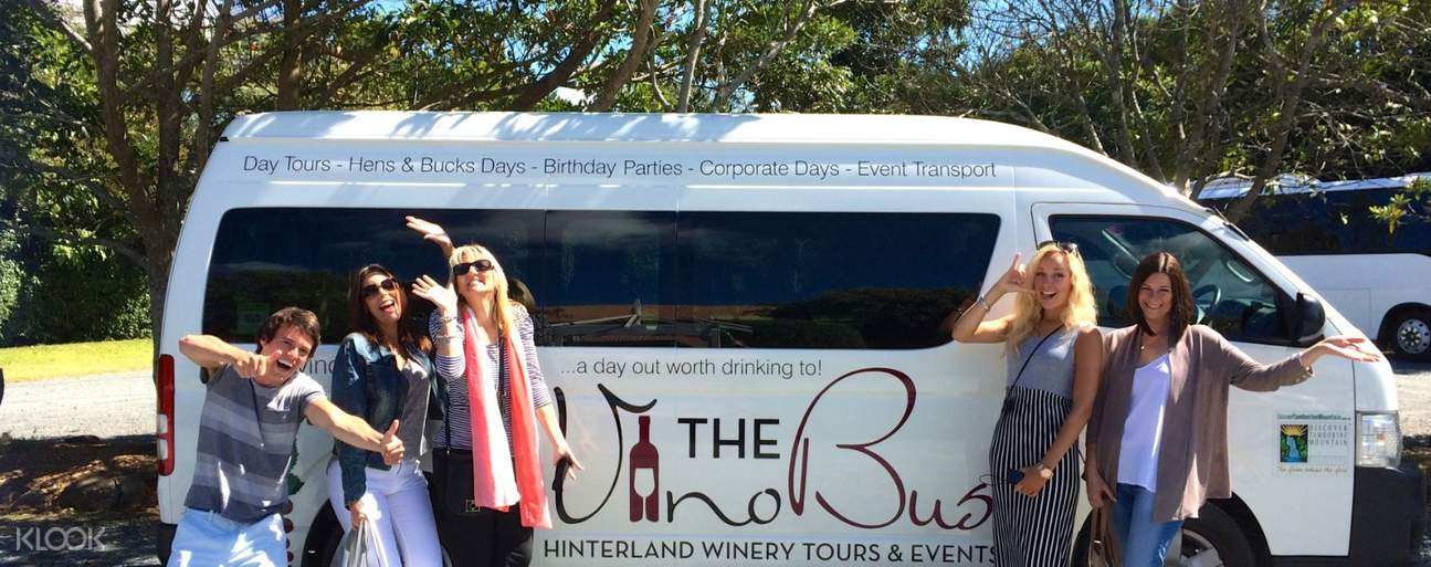 people in front of The Vino Bus tour vehicle
