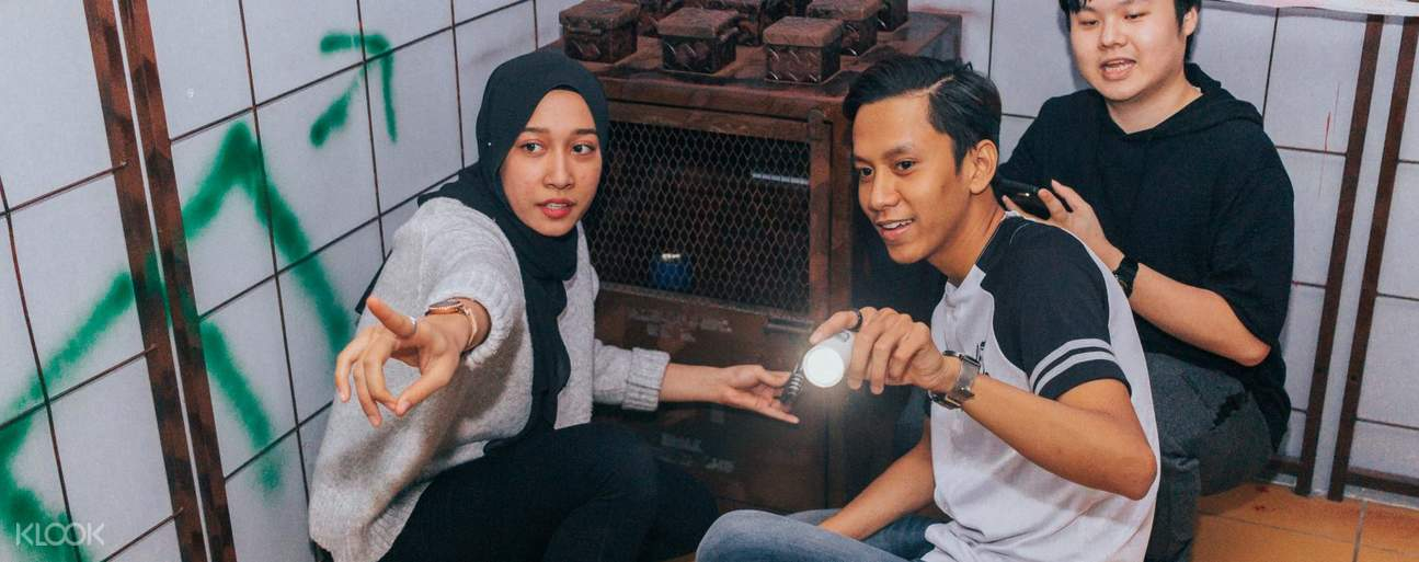 People crouching down next to box in Escape Room Kuala Lumpur