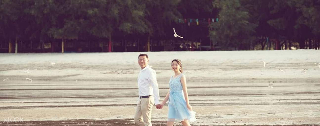 Man and woman walking along beach