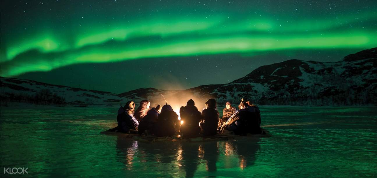 group of people on a northern lights chase