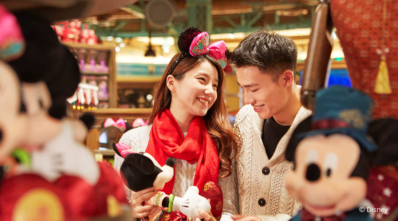 young couple looking at Mickey stuffed toys