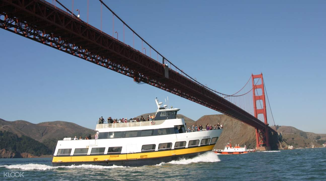a cruise boat passing under the Golden Gate Bridge in San Francisco