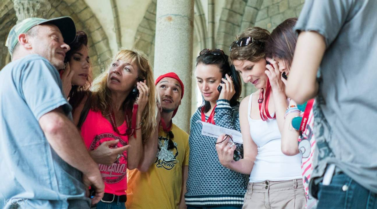 tourists inside the Mont-Saint-Michel listening to their audio guides