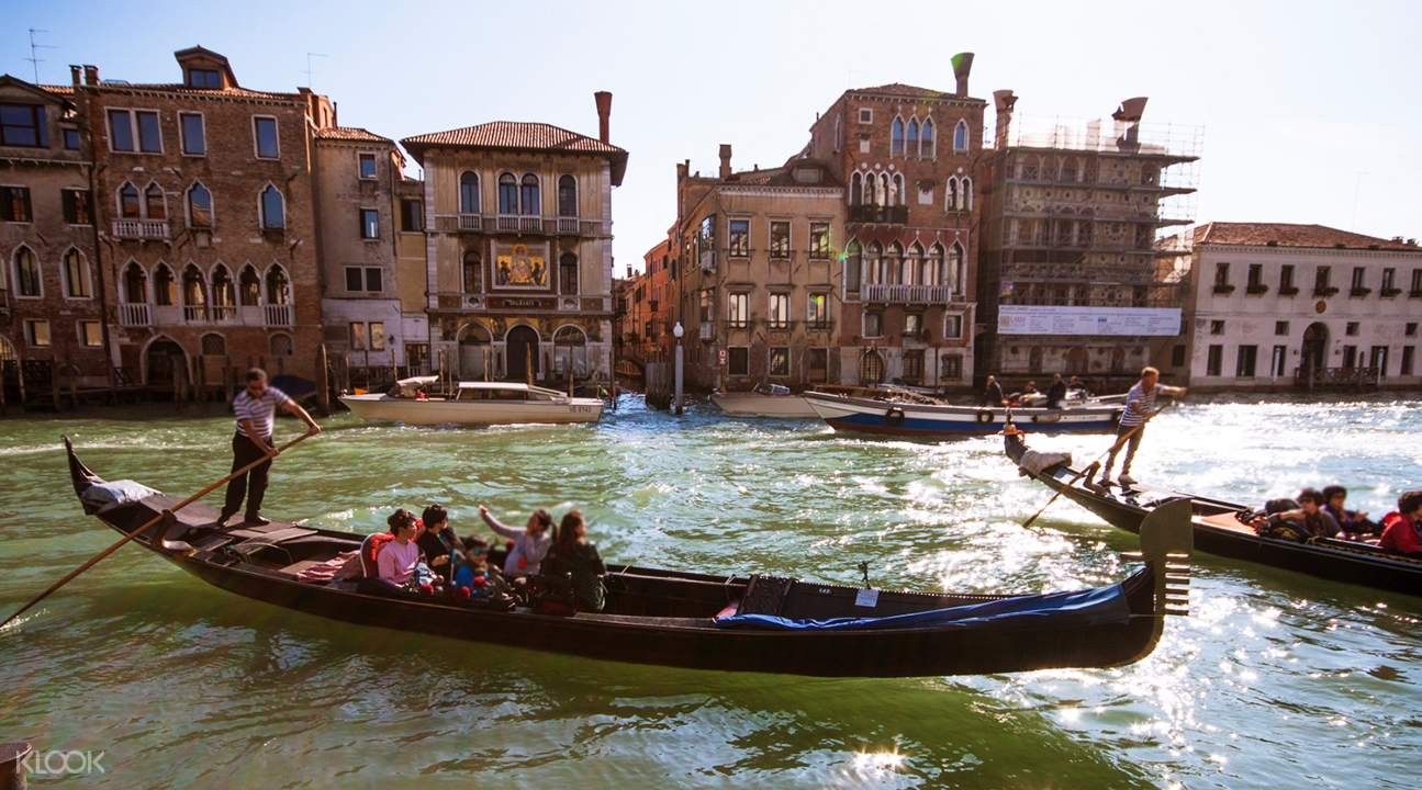 gondola in the middle of a Venetian canal with houses in the background