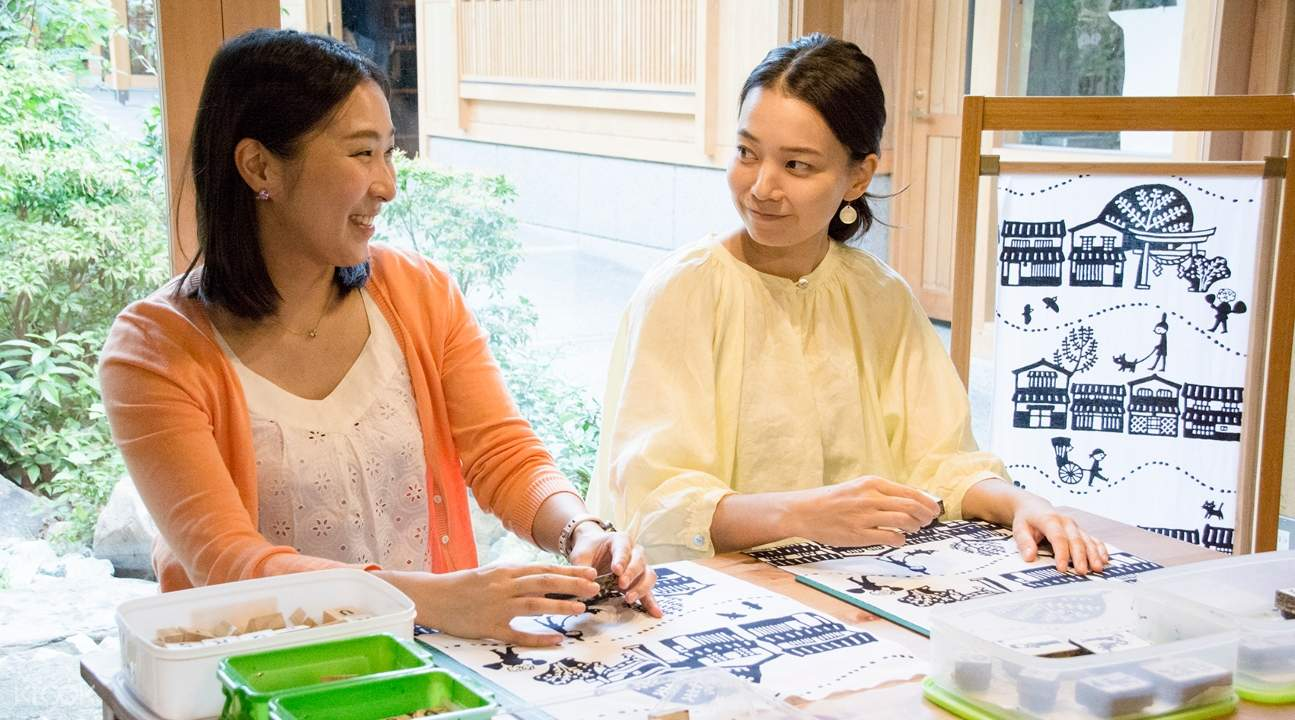 two women smiling at each other while making Japanese cotton towels