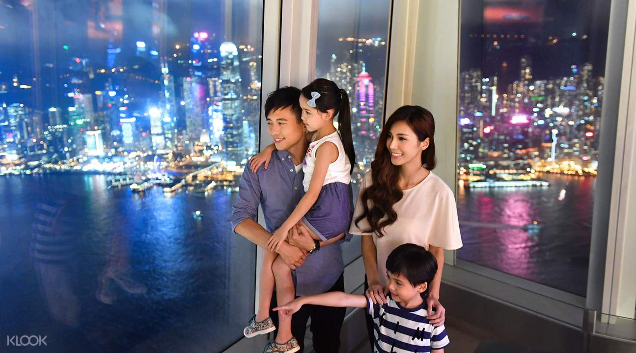 family viewing the Hong Kong skyline at night at the Sky100 Observation Deck