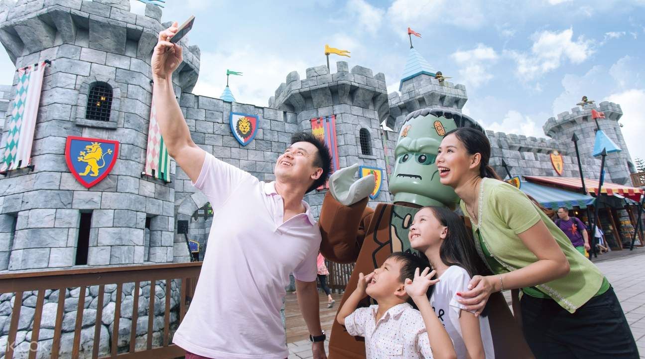 people taking pictures with a LEGOLAND® Malaysia mascot