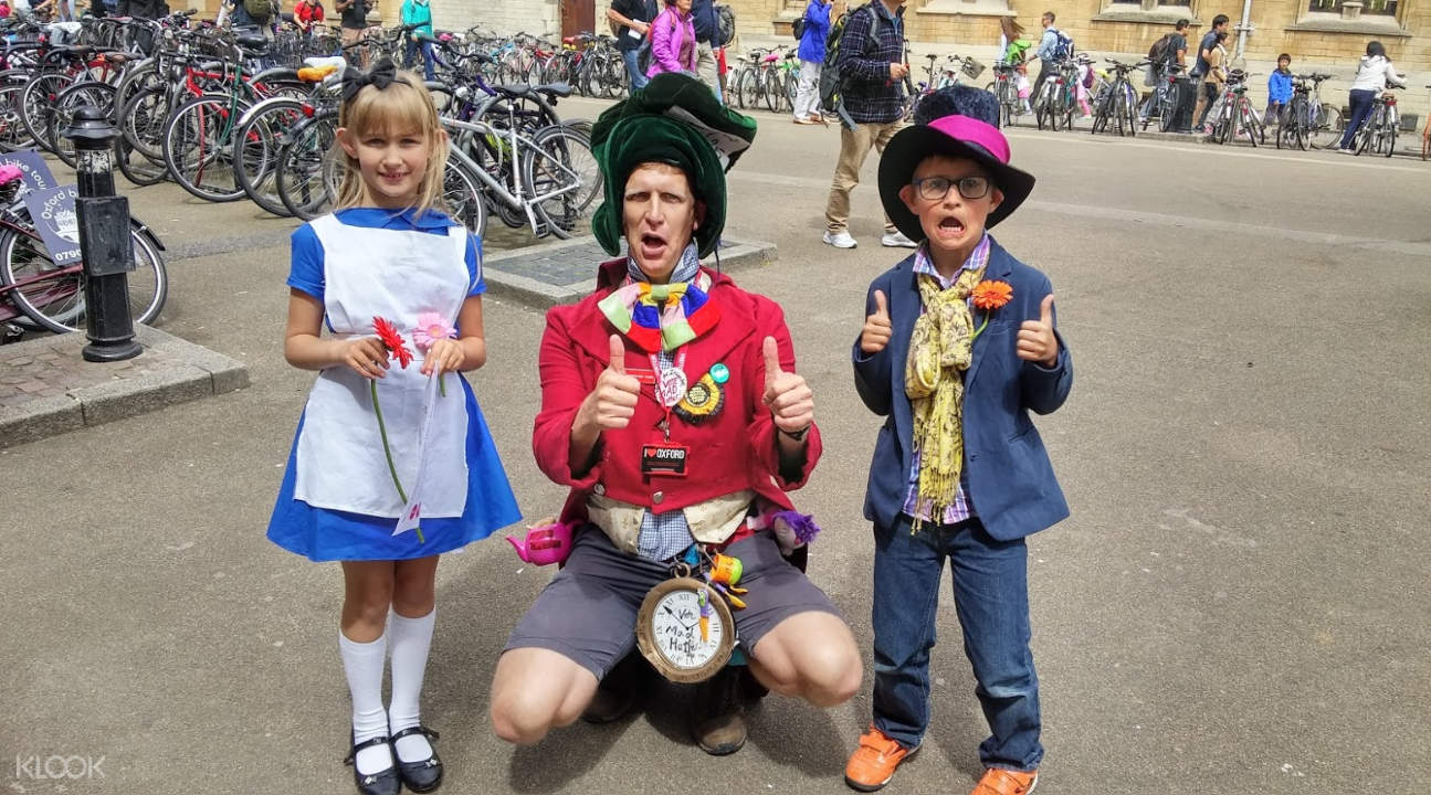 a man and two children wearing Alice in Wonderland costumes