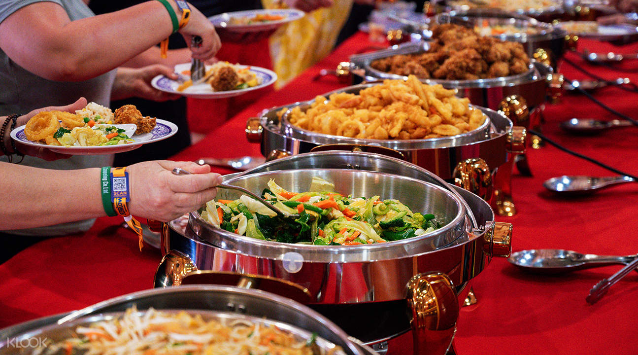 person grabbing food on buffet table