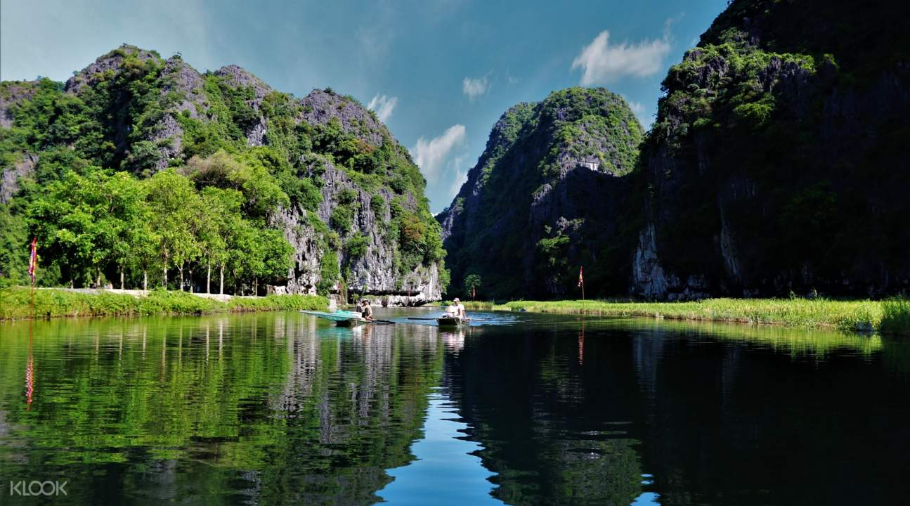 boats cruising in the river against limestone mountains