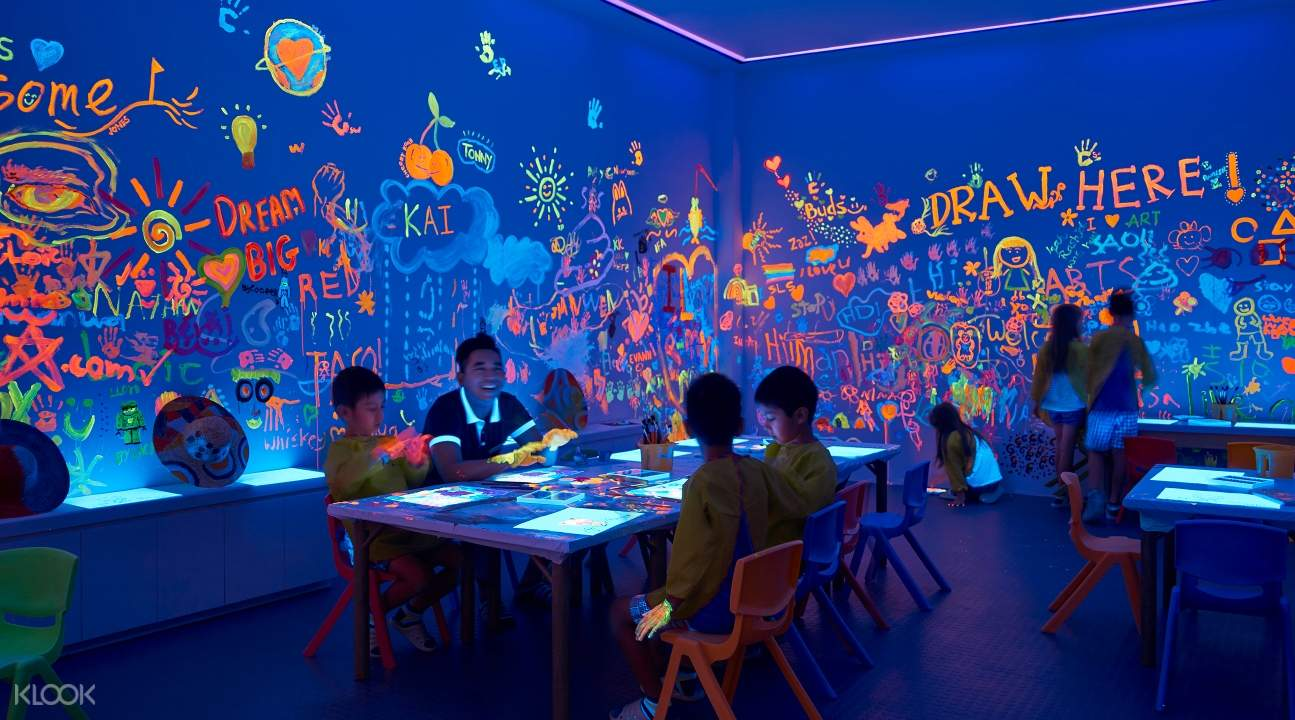 a room lit up by glow in the dark paint; a bunch of kids are painting