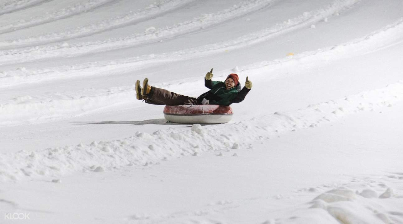 a person on a tube sliding down a snowy hill while giving the two thumbs up