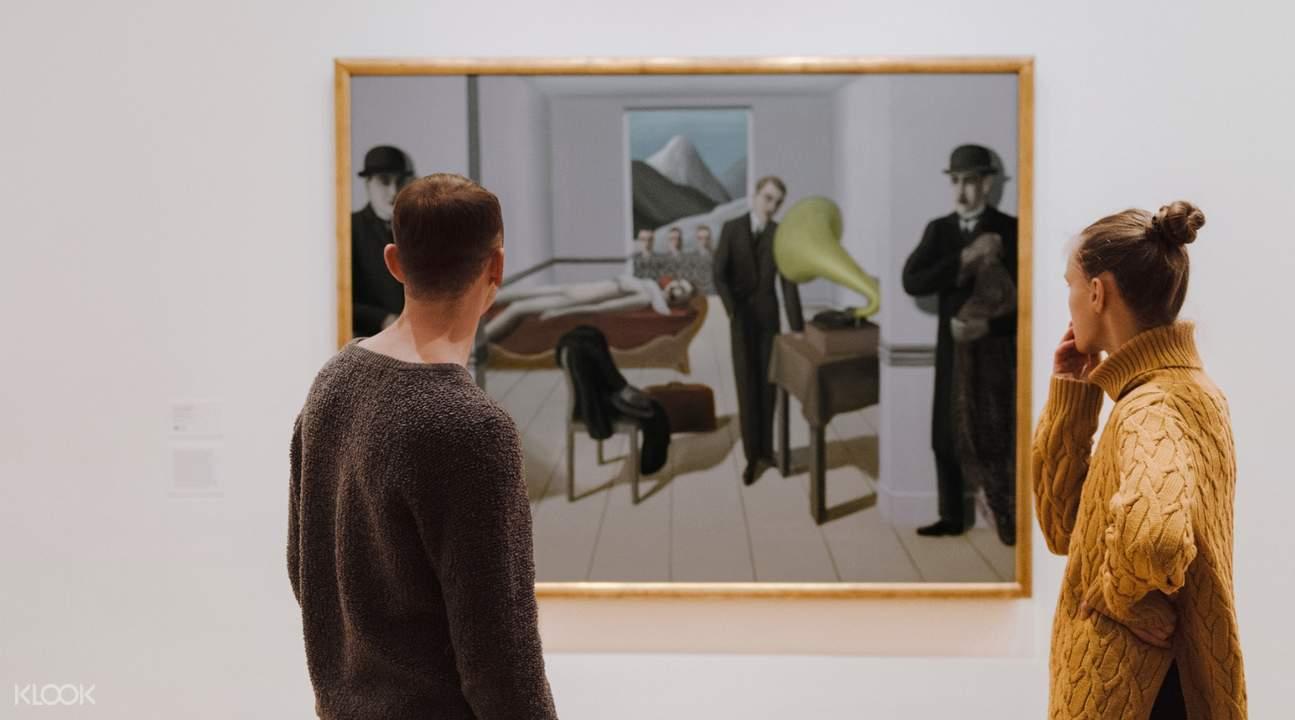 visitors viewing a painting at the moma