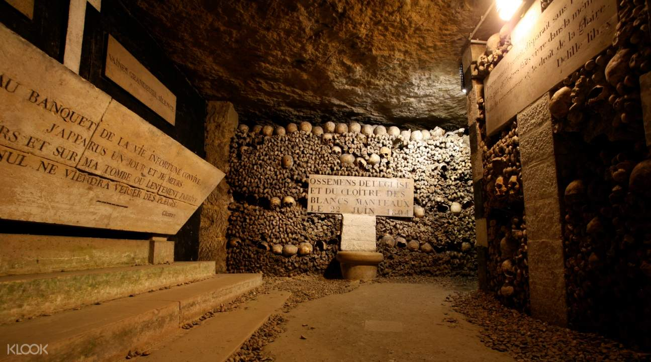 a hallway with signs in the Catacombs; the walls are adorned with skulls and bones