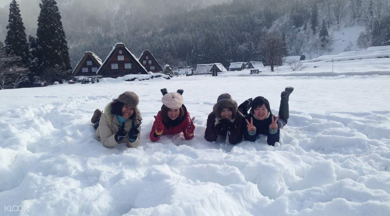 four guests playing in the snow in Ogimachi Village