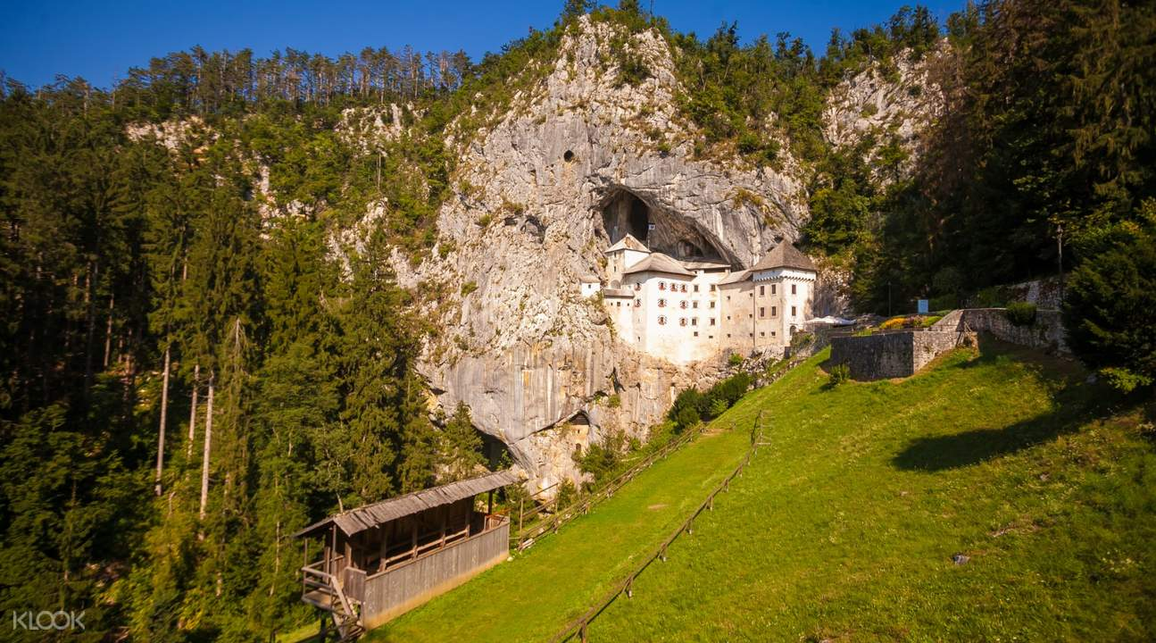 Predjama Castle with trees and mountains