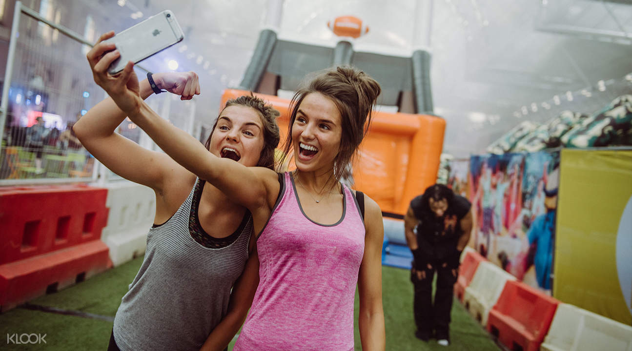 two girls taking selfies after completing the obstacle course