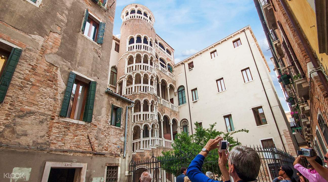 a view of the Scala del Bovolo with tourists taking pictures of it